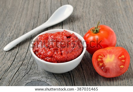 Tomato sauce in a white bowl and fresh tomatoes on wooden background - stock photo