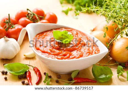 Tomato sauce in a white sauce boat with fresh ingredients, including tomatoes, herbs, garlic and spices - stock photo