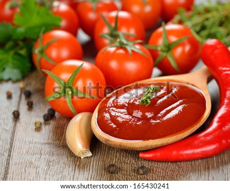 tomato sauce in a wooden spoon on brown table - stock photo