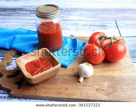 tomato sauce in mason jar with sauce inside a wooden bowl. Fresh stem of oregano with a bulb of garlic  tomatoes on the vine on a wooden cutting board /tomato sauce with tomatoes/Italian Tomato sauce - stock photo