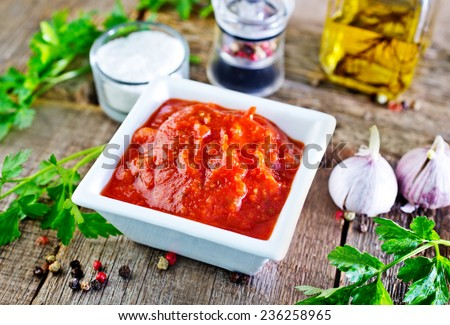 tomato sauce in white bowl and on a table - stock photo