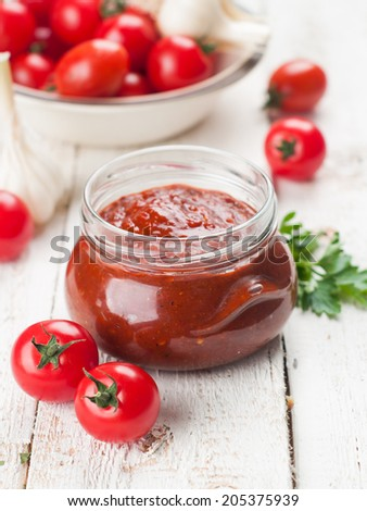 Tomato sauce (jam) with parsley and garlic in glass jar, selective focus - stock photo