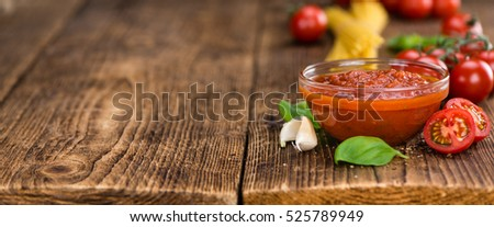 Tomato Sauce on rustic wooden background (close-up shot)