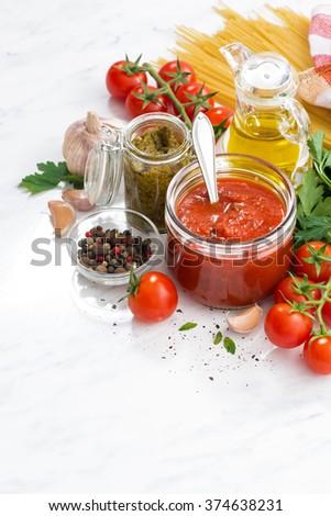 tomato sauce, pesto and ingredients for pasta, vertical, closeup - stock photo