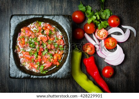 Tomato sauce salsa and ingredients dark stone background. Top view - stock photo
