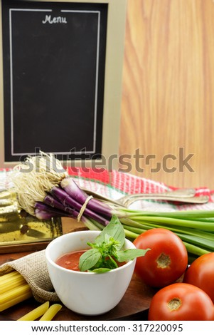Tomato sauce with herbs and blackboard, with copy-space - stock photo