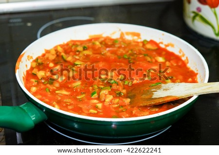 Tomato sauce with vegetable pieces in a green frying pan