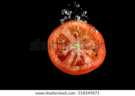 Tomato slice falling into water at black background - stock photo