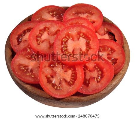 Tomato slices in a wooden bowl on a white background