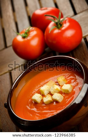 Tomato soup in a earthenware bowl with tomatoes