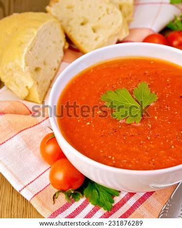 Tomato soup in a white bowl with a spoon on a napkin, parsley, bread on a wooden boards background