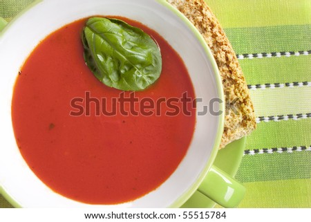 Tomato soup in green bowl with basil and crouton. - stock photo