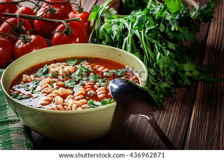 Tomato soup noodles in the bowl on a wooden table - stock photo