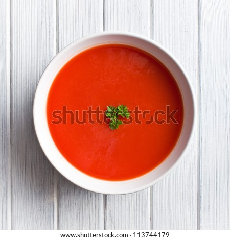 tomato soup on kitchen table. top shot - stock photo