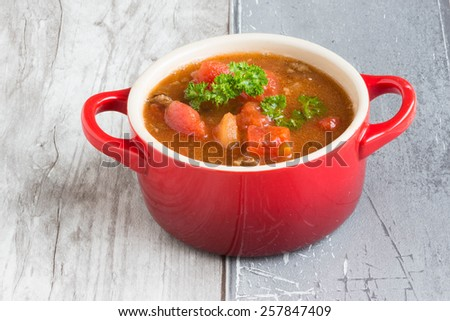 Tomato soup on wooden table - stock photo