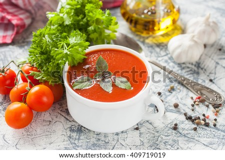tomato soup with a basil in a bowl on a table, selective focus - stock photo