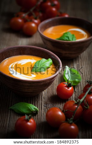 Tomato soup with cream and fresh basil  - stock photo