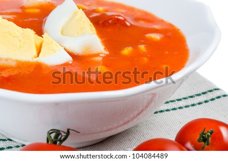 Tomato soup with eggs in white bowl - stock photo