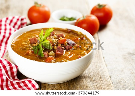 Tomato soup with lentils and sausages - stock photo