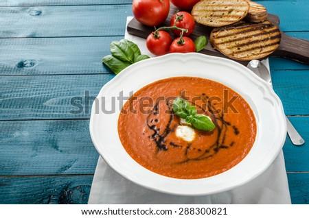 Tomato soup with mozzarella, balsamic winegrad and basil, bruschetta toasts - stock photo