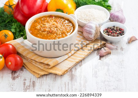 tomato soup with rice and vegetables on a white wooden background, horizontal - stock photo