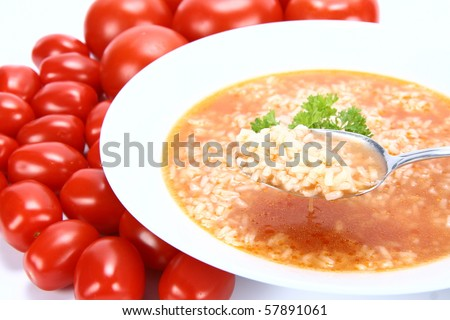 Tomato soup with rice decorated with parsley (some of it on a spoon) with fresh tomatoes - stock photo