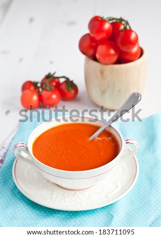 Tomato soup with tomatoes on the background on the white table, selective focus - stock photo