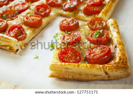 Tomato tart, puff pastry topped with mustard, cheese and cherry toamtoes. - stock photo