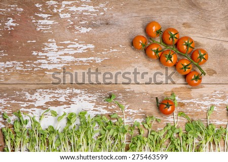 Tomato with Pea Sprout on wood top - stock photo