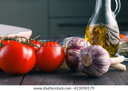 Tomatoes and garlic on wooden black table  background - stock photo
