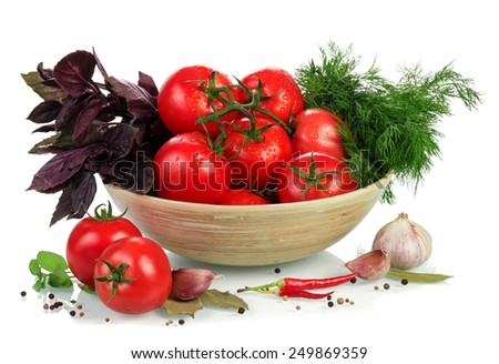 Tomatoes and herbs in bowl isolated on white background - stock photo