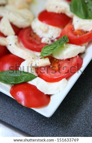 Tomatoes and mozzarella cheese arranged in an alternating pattern on a plate on a buffet table - stock photo