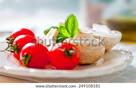 Tomatoes and mushrooms on white wooden table - stock photo
