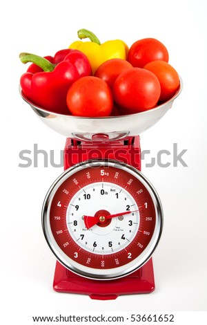 Tomatoes and peppers on old fashioned weighing scales - stock photo