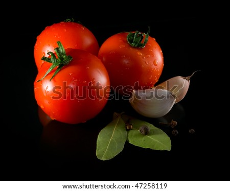 Tomatoes and spices on a black background. Isolated path included. - stock photo