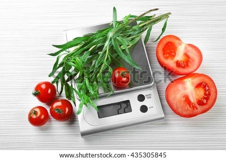 Tomatoes and tarragon with digital kitchen scales on wooden background - stock photo