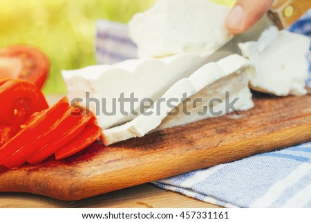 tomatoes and white cheese on wooden table