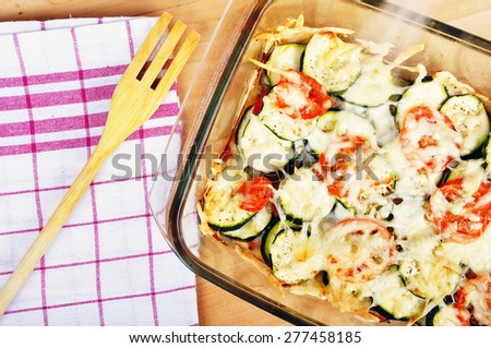 Tomatoes and zucchini baked with cheese in a ovenproof dish - stock photo