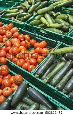 Tomatoes and zucchini in crates in a shop