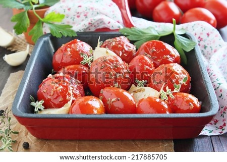 Tomatoes baked with spices, herbs ,garlic and olive oil on a wooden background. - stock photo