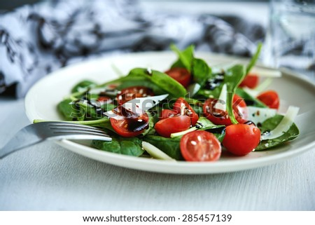 tomatoes, cheese and spinach salad with balsamic dressing - stock photo