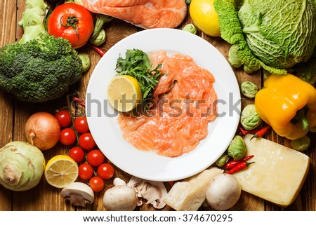 tomatoes, cherry tomatoes, salmon soup, blue onion, onions, broccoli, peppers, chili, wood board, white tureen, red pepper, garlic, salmon steak, rosemary - stock photo