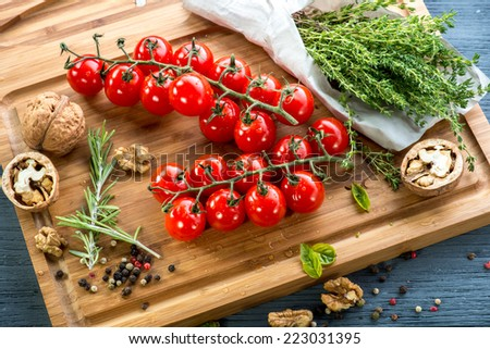 Tomatoes cherry with spices and nuts on wooden desk