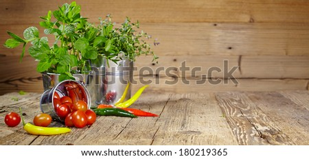 Tomatoes, chives and chili peppers on a wooden table top  - stock photo
