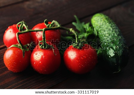 Tomatoes, cucumber and arugula on wooden background - stock photo