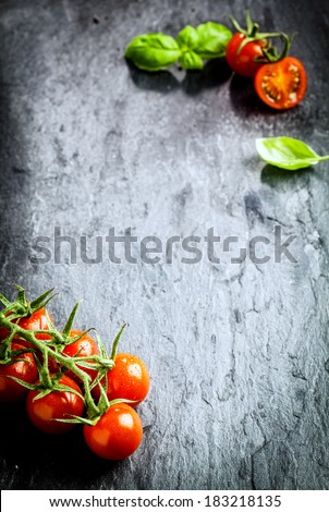 Tomatoes from above. Fresh delicious red tomatoes with basil on black stone background with copyspace - stock photo