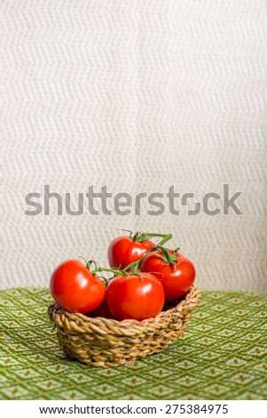 Tomatoes in a basket on a green tablecloth vintage style
