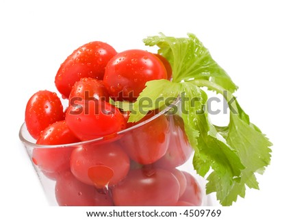 Tomatoes in a glass with leafy celery stalk