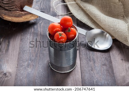 Tomatoes in a preserve tin on a back table - stock photo