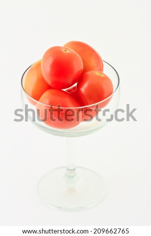 Tomatoes in glass on white background - stock photo